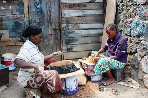Deux femmes dans l'atelier s'occupent de fabriquer les bols d'argile et de les percer