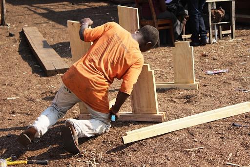 15) Un jeune entrain de fabriquer un cadre pour une chaise