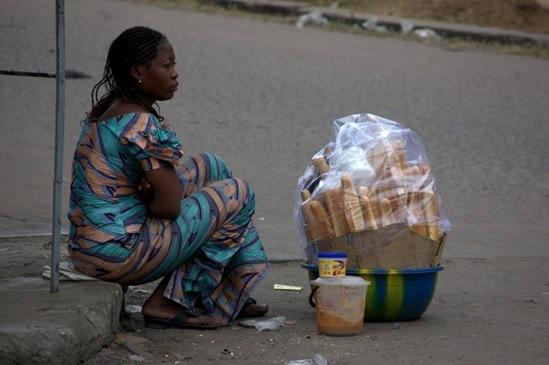 Tôt le matin, une femme s'assoie au bord de la route pour vendre les pains aux premiers passants