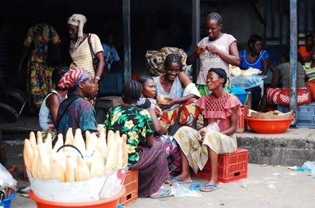 Des mamans vendeuses qui se reposent et qui discutent sourire aux lèvres assises sur leurs bacs dans l'enceinte de la boulangerie